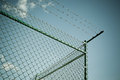 Razor and barbed wire fence a chain link topped by horizontal shot Stock Photo