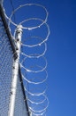 Razor wire fence topped metal mesh with blue sky Stock Photo