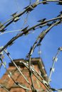Razor wire and old industrial chimney with blue sky Stock Photo