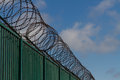 Razor wire on top of green fence guarding french ferry terminal boundary area and dunkirk france europe ferries to the uk Stock Photos