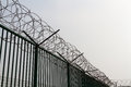 Razor wire on top of green fence guarding french ferry terminal boundary area and to deter refugees asylum seekers dunkirk france Stock Images