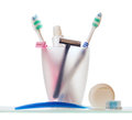 Razors with toothbrushes and toothpaste in cup over white background Royalty Free Stock Photography