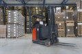 Reach truck driving around cardboard boxes in a warehouse Stock Photos