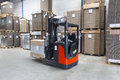 Reach truck driving passing by in a warehouse where cartboard boxes are stored on palets Stock Photography