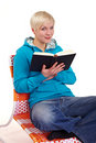 Reading a black book on armchair Royalty Free Stock Photos