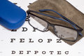 Reading black eyeglasses, brown microfiber cleaning cloth and blue protective case on white eye chart Royalty Free Stock Photo
