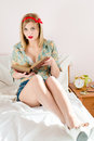 Reading book beautiful blonde pinup young woman girl with red lipstick looking at camera Stock Image