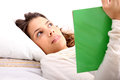 Reading a book in bed young latin woman Royalty Free Stock Photo