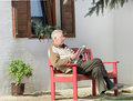 Reading book in courtyard Royalty Free Stock Images