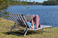 Reading book by the lake young girl on sunbed reads a next to a in värmland sweden Royalty Free Stock Photo