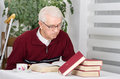 Reading books older man with walking stick sitting in his home and Royalty Free Stock Photography