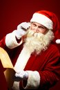 Reading christmas wishes portrait of happy santa claus holding letter in his hands and looking at camera Royalty Free Stock Images