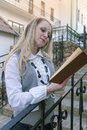 Reading Concepts and Ideas. Portrait of Sensual Caucasian Blond Woman Reading Book Outdoors in City Royalty Free Stock Photo