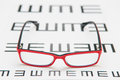 Reading eyeglasses and eye chart close up on a light gray background Royalty Free Stock Photos