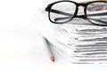Reading eyeglasses with stacking of newspaper background , busin Royalty Free Stock Photo