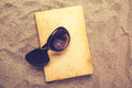 Reading favourite old book on summer vacation beach holiday top view of a and sunglasses in warm snow Royalty Free Stock Photo