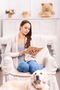 Reading girl in the armchair and her dog around Royalty Free Stock Photo
