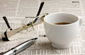 Reading glasses cup coffee silver ballpen laying newspaper Stock Photo