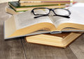Reading glasses on the opened book wooden table Stock Photography