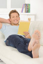 Reading his favorite book handsome young man lying on the couch and a Stock Photo