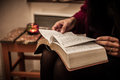 Reading holy bible on vintage table with candle closeup Royalty Free Stock Images