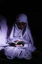Reading koran using torch muslims quran as the source of the light in solo central java indonesia Stock Images