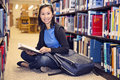 Reading in the library asina student sitting and book Royalty Free Stock Photo