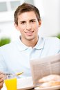 Reading man eats dieting breakfast in kitchen newspaper at the table Stock Images