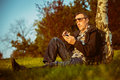 Reading message middle aged man sit in nature on his smart phone Royalty Free Stock Photo