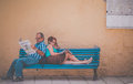 Reading newspaper on the bench midlife couple sitting a and newspapers during afternoon siesta gran canaria spain europe Royalty Free Stock Image
