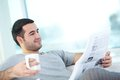 Reading newspaper a young guy with it Royalty Free Stock Photo