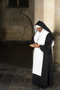 Reading nun in habit the bible a medieval church Stock Photo
