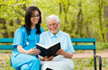 Reading with patient caring doctor kind elderly lady sitting on a bench a book Royalty Free Stock Photography