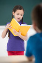 Reading to the class. Confident little schoolgirl reading a book Royalty Free Stock Photo