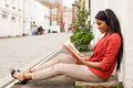 Reading young woman a book and listening to music Stock Photography
