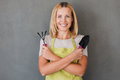 Ready for gardening happy mature woman in green apron holding equipment and smiling while standing against grey background Stock Image