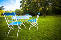 Ready for picnic a table and some empty chairs on a green meadow in summer Stock Photography