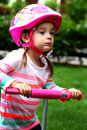 Ready set go a closeup of a sweet little toddler girl with pigtails wearing a pink helmet to on a pink scooter shallow depth of Royalty Free Stock Photos