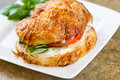 Ready to eat chicken salad sandwich on plate horizontal photo of a tomato basil and onion inside croissant bread white square Stock Photography