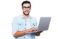 Always ready to help confident young indian man holding laptop and smiling while standing against white background Stock Photography