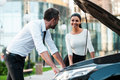 He is always ready to help two smiling young business people looking at each other while leaning at the opened vehicle hoodof the Royalty Free Stock Image