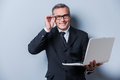 Always ready to help you cheerful mature man in formalwear adjusting his eyeglasses and holding laptop while standing against grey Royalty Free Stock Image