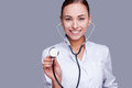 Always ready to help you confident female doctor in white uniform holding stethoscope and smiling while standing against grey Stock Photos