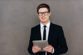 Always ready to help you confident young man in formalwear holding digital tablet and smiling while standing against grey Stock Photography