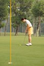 Ready to hit a ball female golf player getting in hole Stock Images