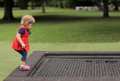 Ready to jump little girl preparing on a trampoline in the park Royalty Free Stock Photo