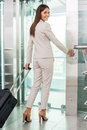 Ready to new business trip rear view of confident young businesswoman in formalwear pushing button while standing near elevator Royalty Free Stock Photos