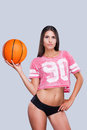 Ready to play attractive young female cheerleader holding basketball ball and looking at camera while standing against grey Stock Photo