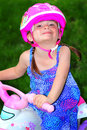 Ready to ride a closeup of a sweet prissy little toddler girl with pigtails in a pretty blue sundress wearing a pink helmet Stock Photo