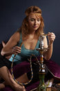 Ready to smoking hookah young woman in style of hippie in interior location like room or house Stock Photo